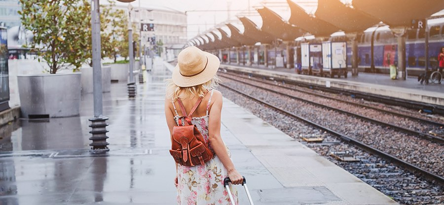 travel by train, woman with luggage waiting on platform