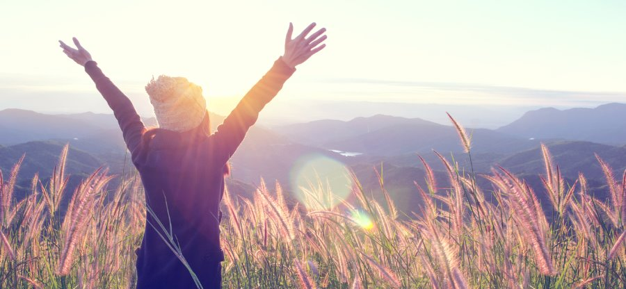 happy-woman-enjoying-nature-on-meadow-on-top-of-mountain-with-sunrise-picture-id897954642 (1)