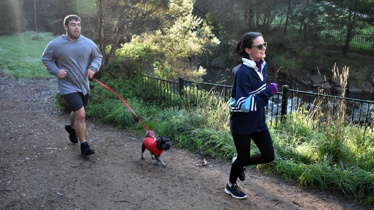 A woman runs ahead of a man with a small dog.