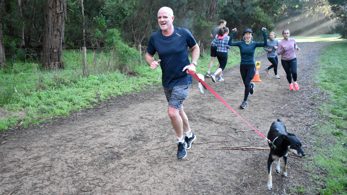 A group of runners turn at the turn around cone. In the foreground a smiling man runs with a dog. Behind him a woman cheers and holds up her arms.