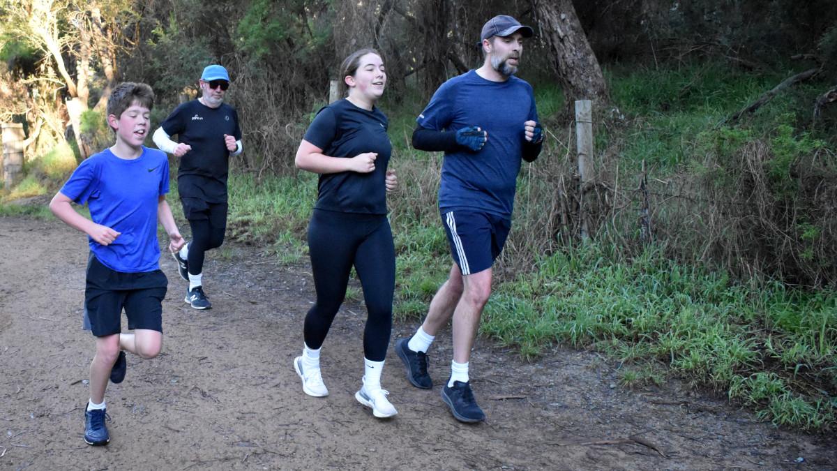 A man runs beside two juniors. Another man runs behind them.