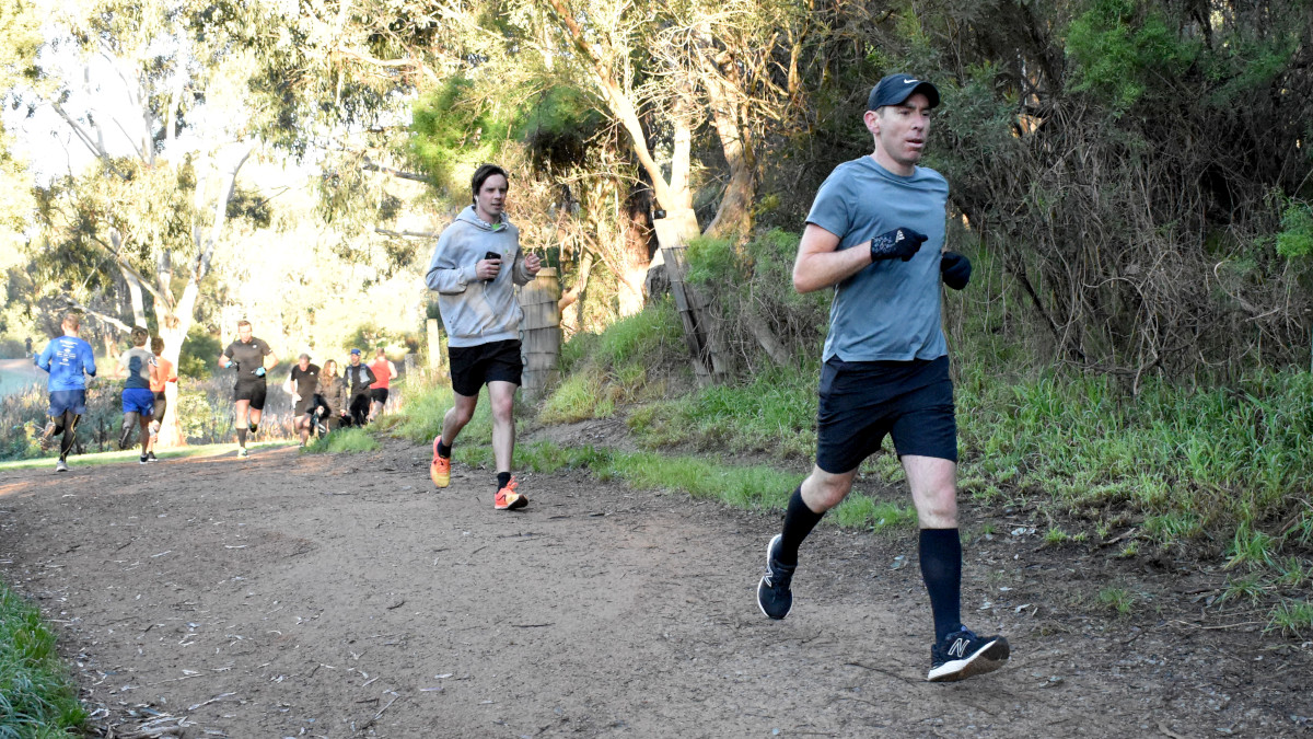 Two men lead a bunch of runners around a bend in a gravel path.