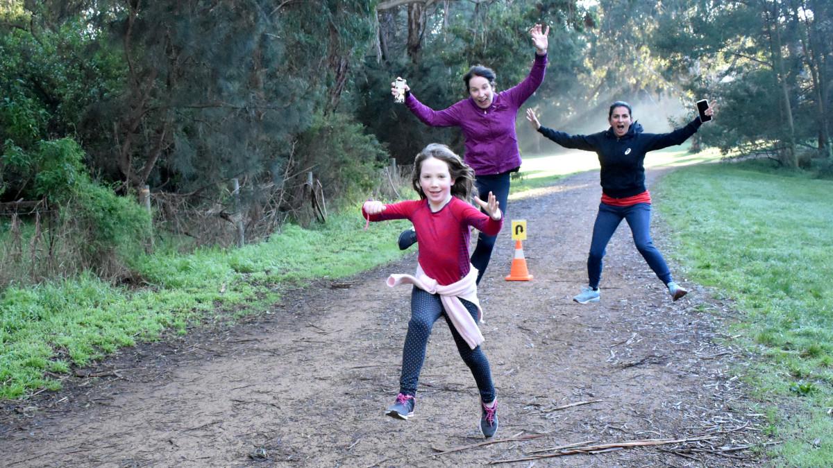 In the foreground a girl jumps. In the background two women jump.