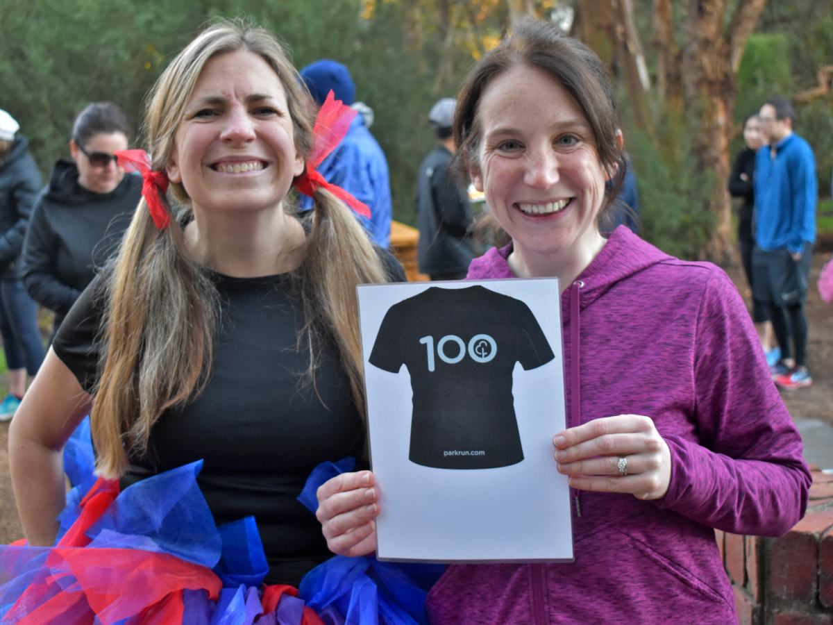 Kate and Olivia standing together holding the 100 parkruns sign