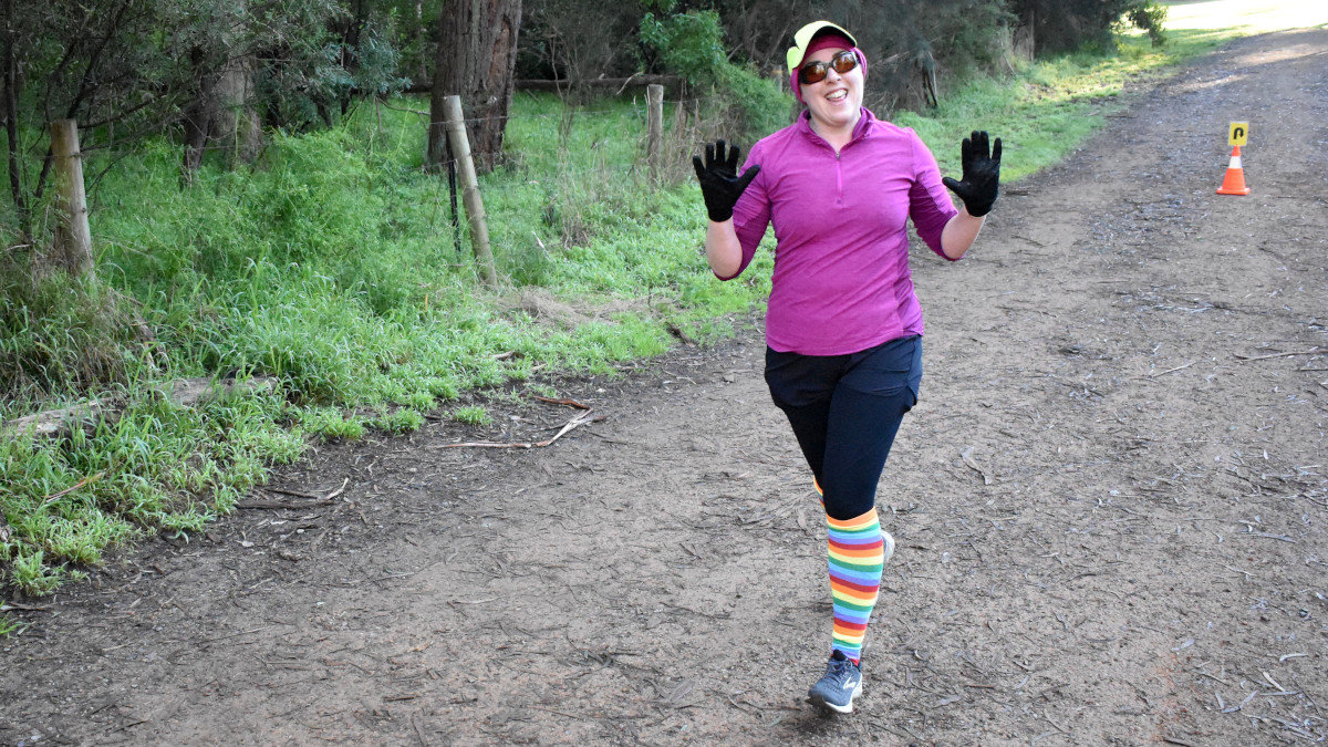 A woman wearing long brightly coloured rainbow socks smiles and waves both hands at the camera.