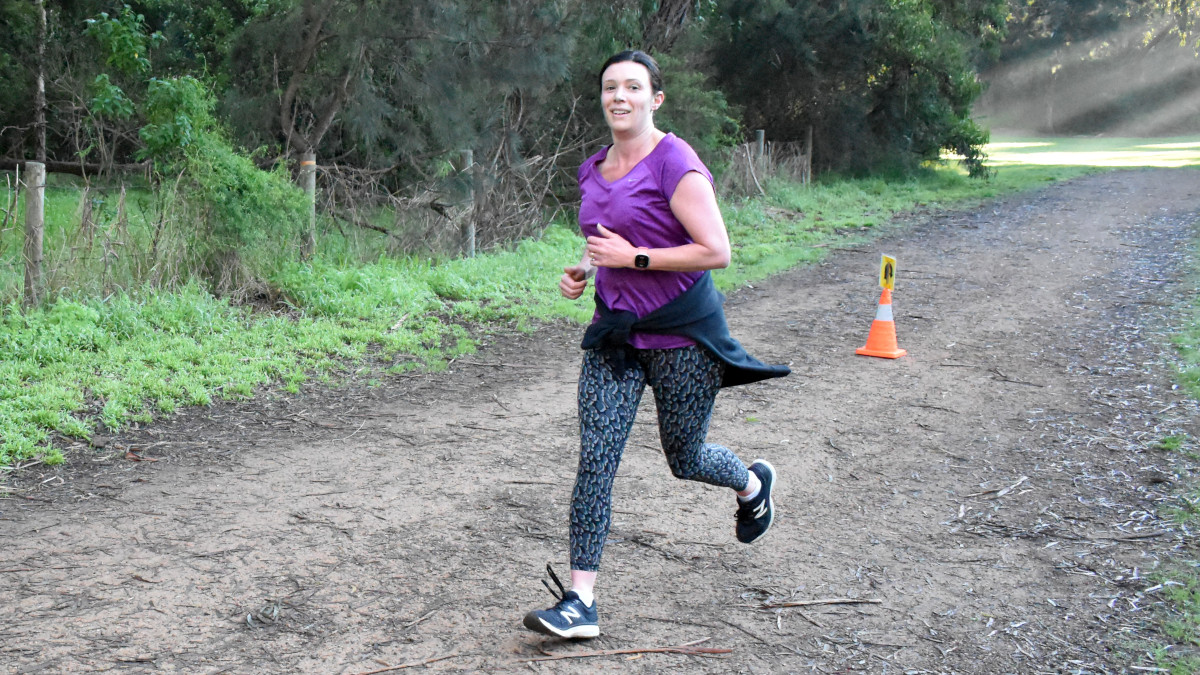 A woman wearing a purple T-shirt runs away from the turn around cone.