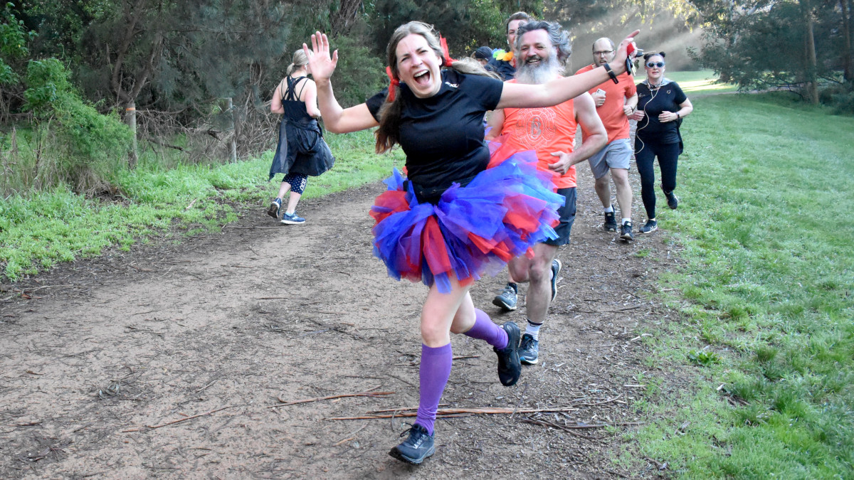 A the head of a large group, a parkrunner wearing a red and blue tutu smiles and waves at the camera.
