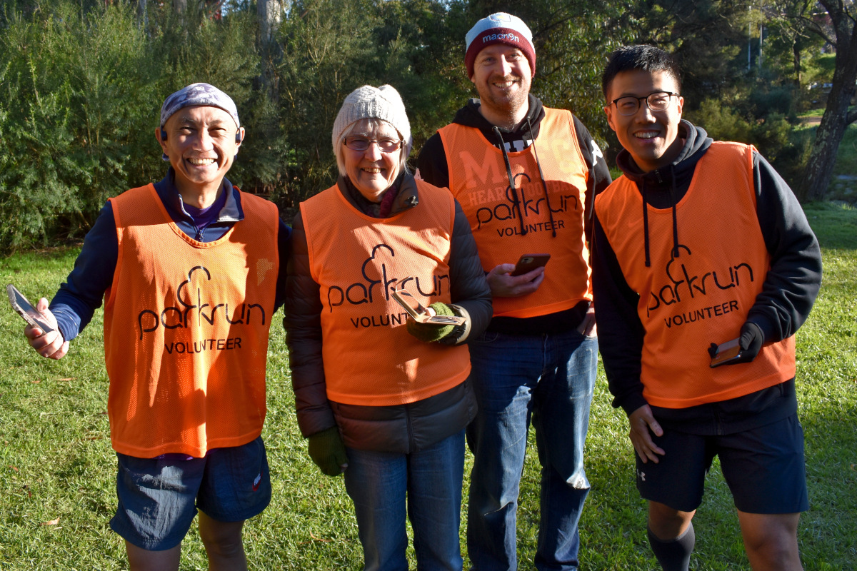 Four volunteers wearing orange vests pose for the photo