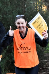 A smiling volunteer holds up a sign saying: First time at Gardiners Creek? Come chat with me.
