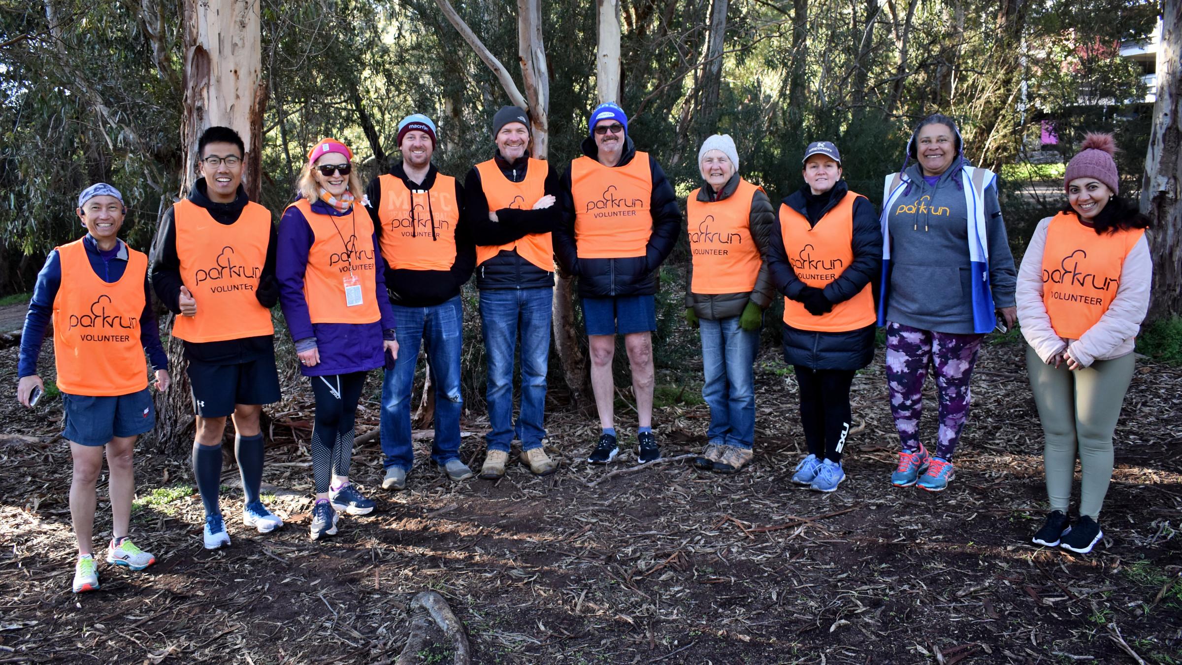 Ten volunteers wearing orange vests line up for the photo.