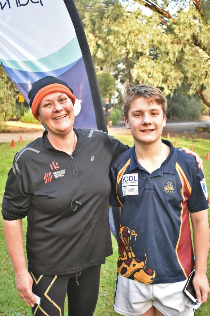 Mother and son parkrunners pose in front of the parkrun finish line.