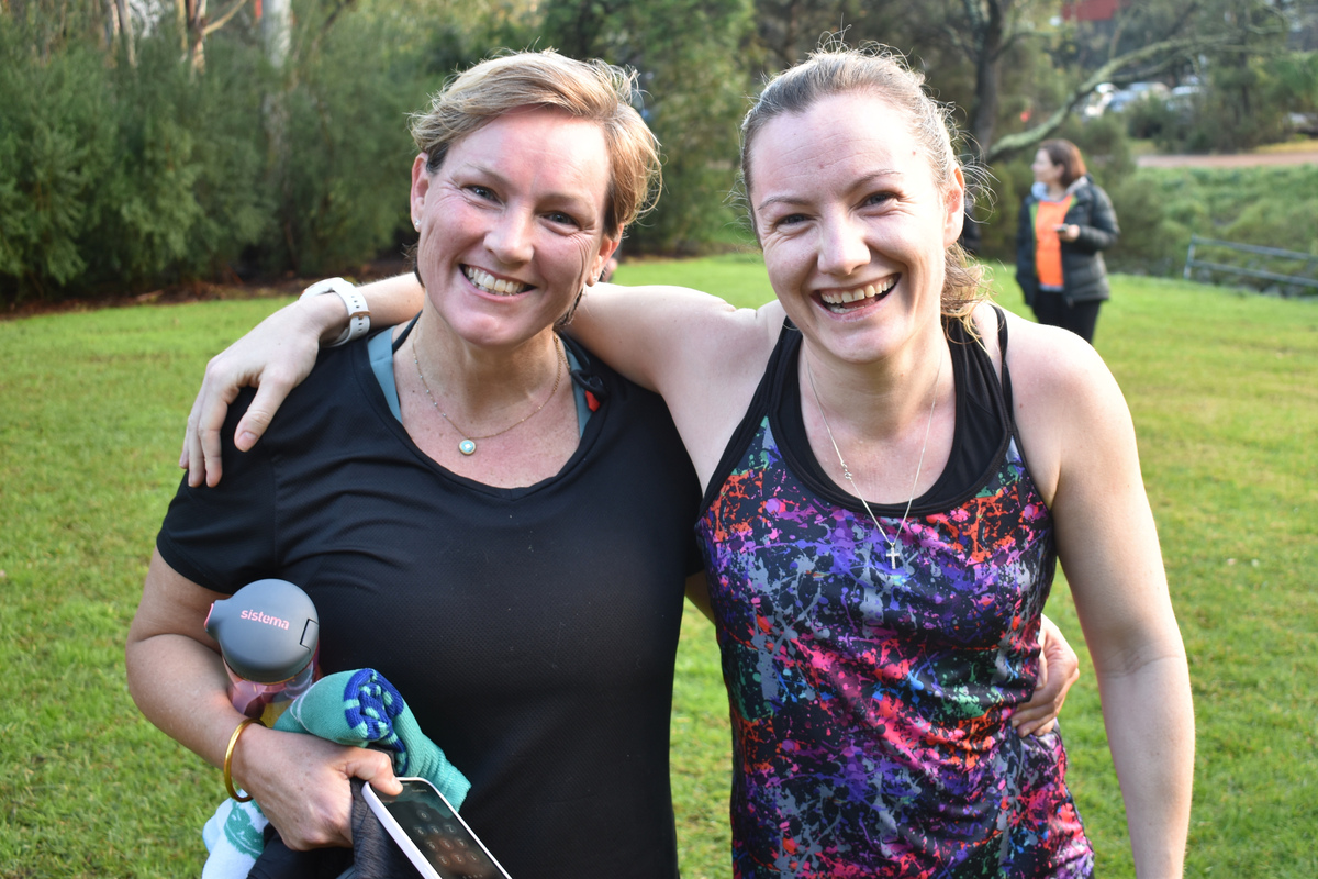 Two parkrunners stand with arms around each other's shoulders in the finish area.