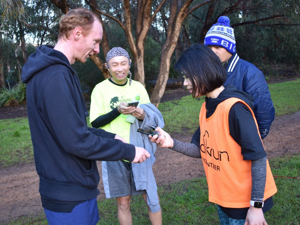A volunteer scans a finish token while two other parkrunners watch.