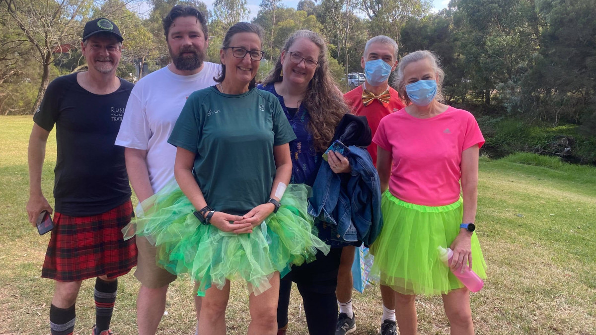 Wendy wears a green milestone T-shirt and green tutu, as she poses with a small group of friends.