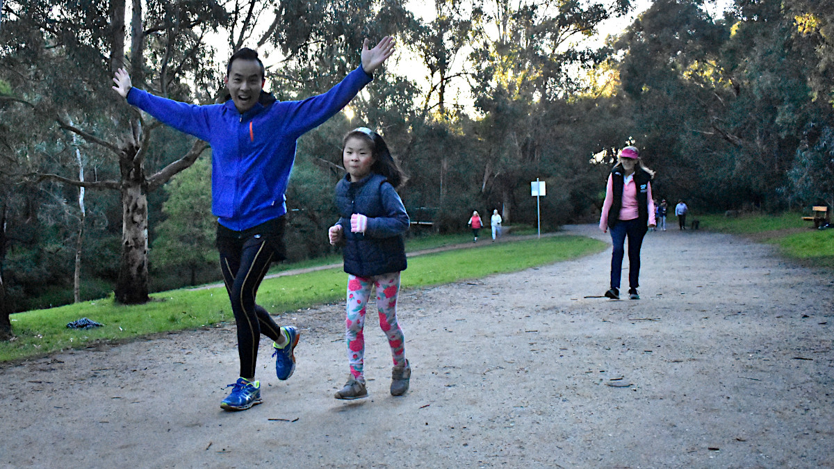 A father and daughter run together. The man holds up both arms to wave to the camera.