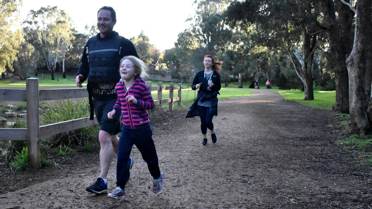 A father and daughter run together.