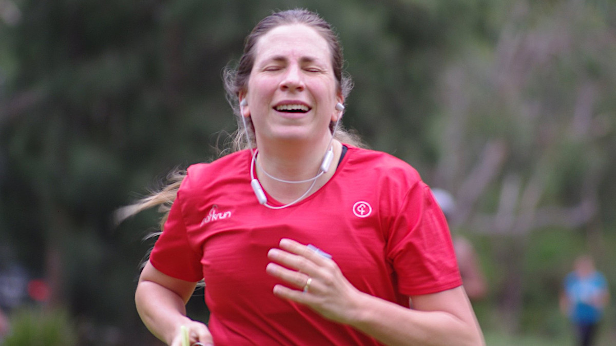 Portrait of a woman running wearing a red t-shirt and white earbuds.