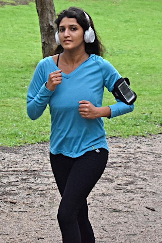 A woman runs, wearing over-ear headphones.