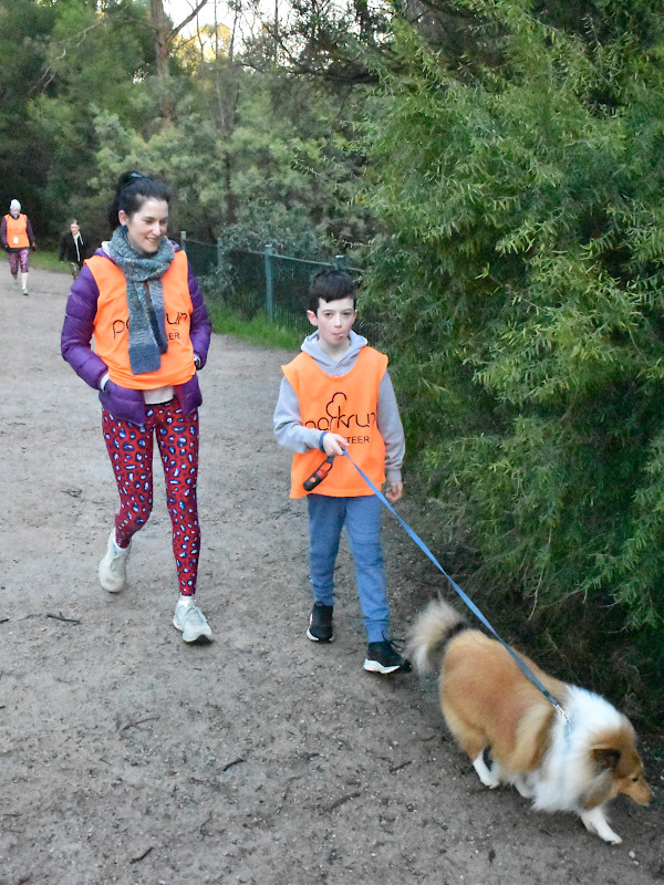 A mother and son wearing volunteer vests walk with a dog.