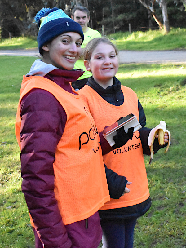 A woman and a girl wearing volunteer vests at the finish line.