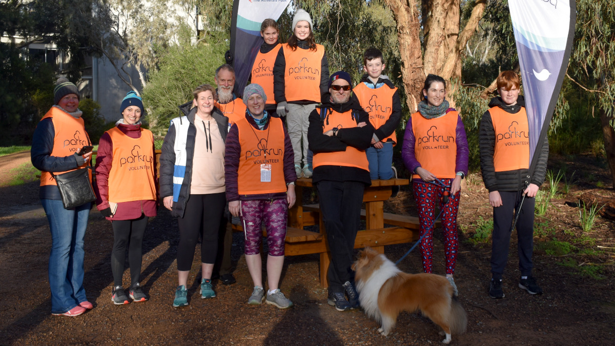 Eleven volunteers and a dog lined up for a group photo.