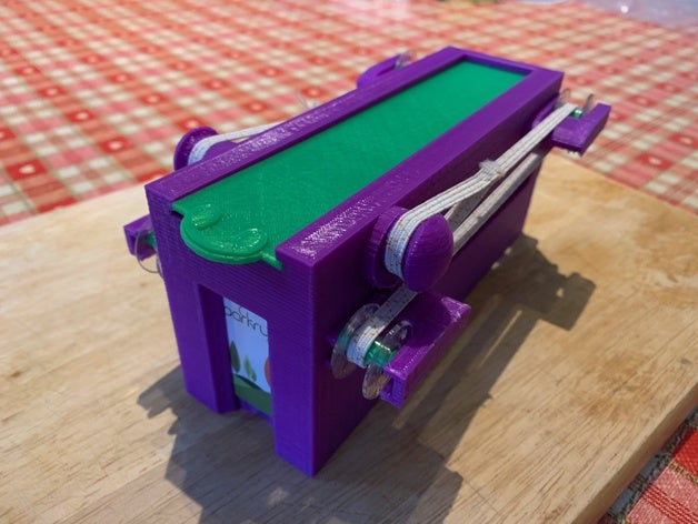 The dispenser is a purple plastic box with a green lid and elastic straps along the sides. It is a handheld device large enough to hold 140 tokens.
