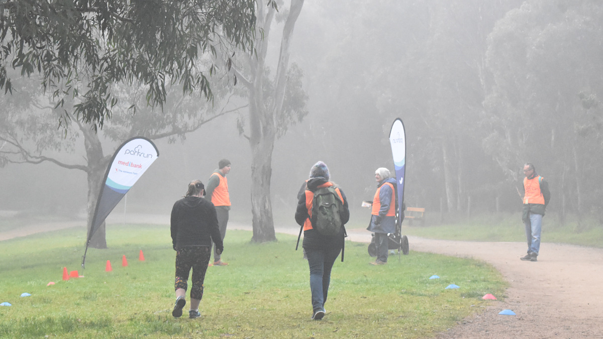Rear view of the tailwalker and a walker approaching the finish line. In the background three volunteers are waiting beside the finish flags. There is fog in the air.