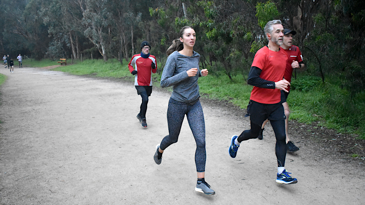 A woman and two men run side-by-side and in step with each other on a wide gravel path. A third man follows closely behind.