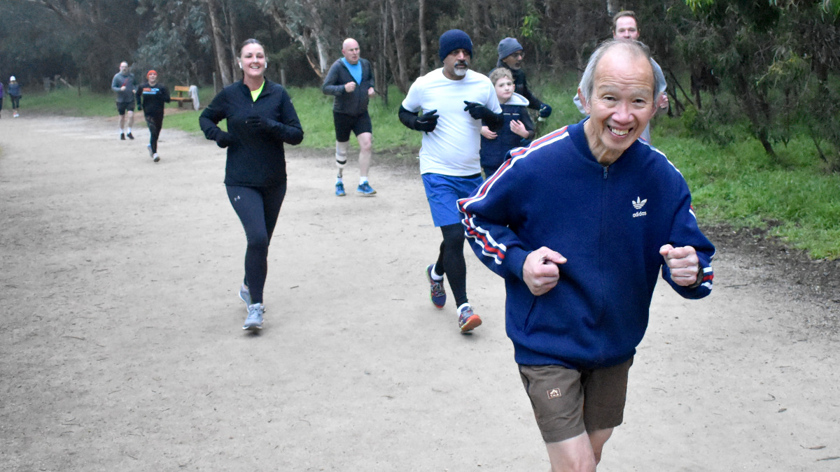 Huan is wearing a blue tracksuit top and brown shorts. He smiles at the camera as he runs ahead of nine other parkrunners spread out behind him.
