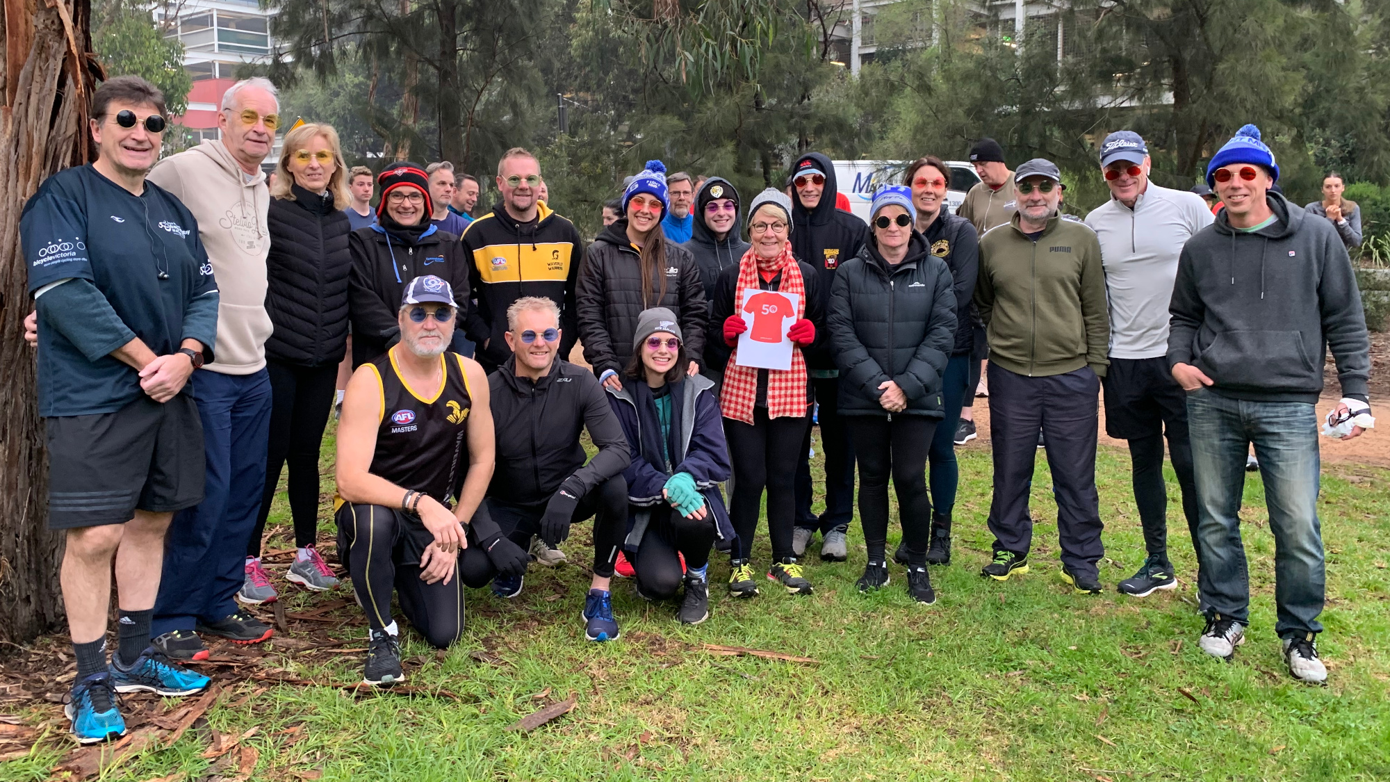 Fiona is wearing a grey beanie and a red-white checked scarf as she holds up the 50 parkruns milestone sign. She stands among a group of sixteen friends who are all wearing novelty glasses that resemble Fiona's round-rimmed spectacles.