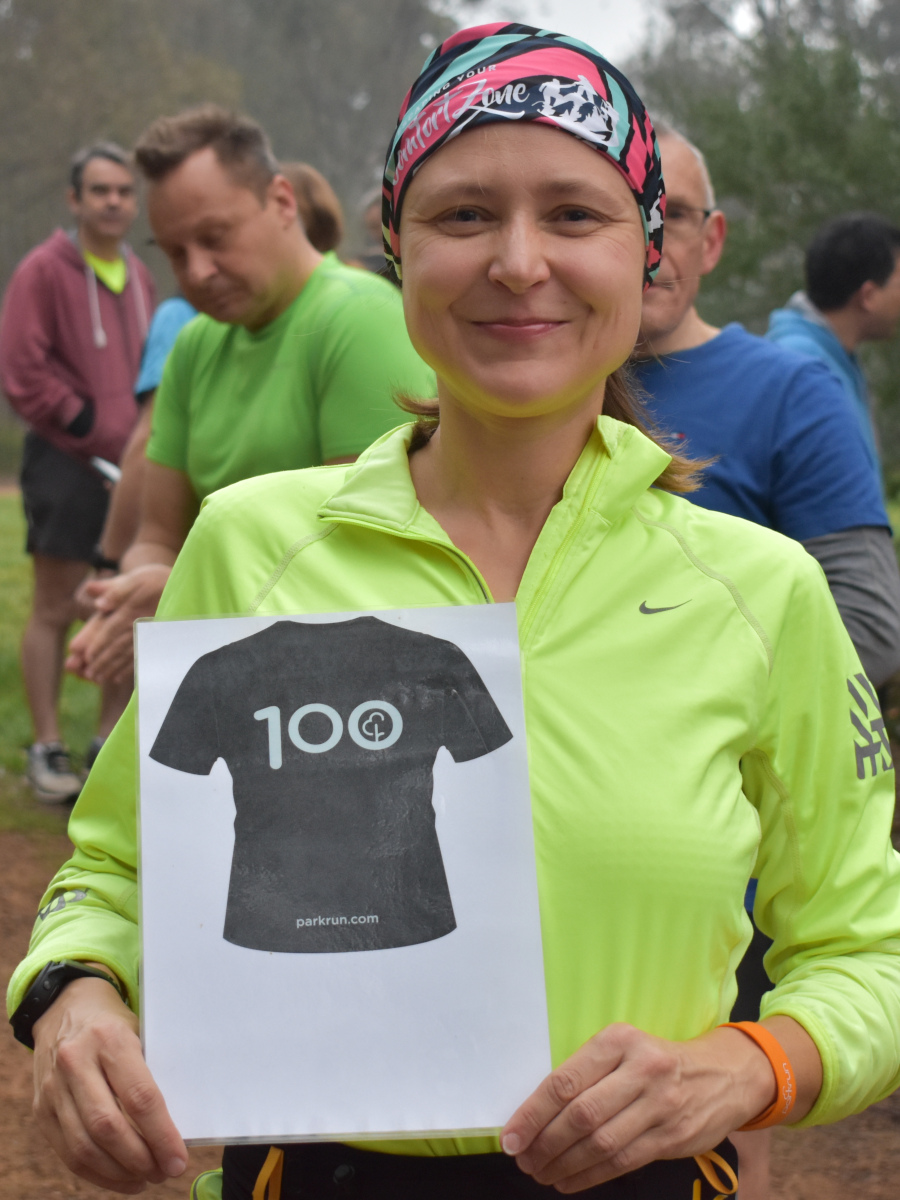 Nadya wears a multi-coloured headband and a yellow long-sleeve running top. She holds the 100 parkruns milestone sign.