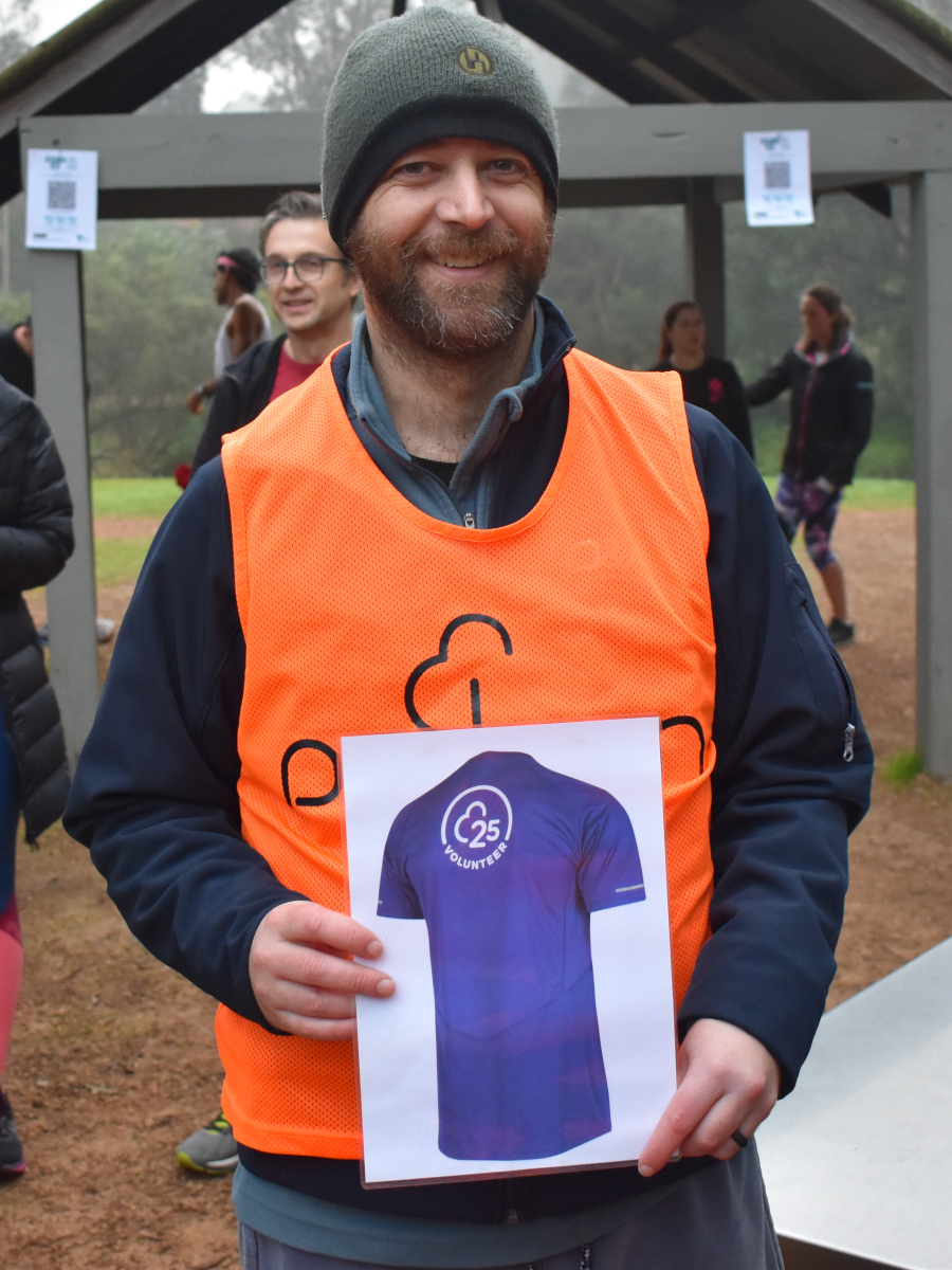 Rob wears a grey beanie and an orange volunteer vest over a blue jacket. He holds the 25 Volunteer milestone sign.