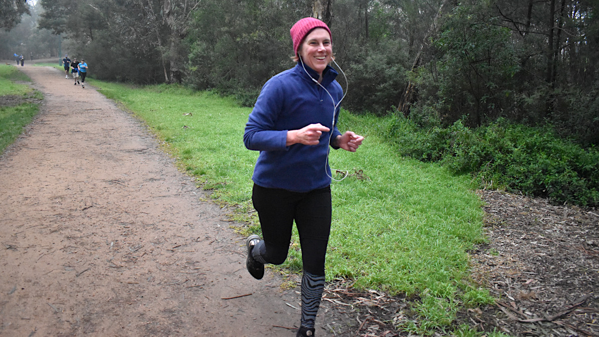 A woman wearing a blue long sleeve top, black running tights and a pink beanie smiles as she runs along  gravel path.
