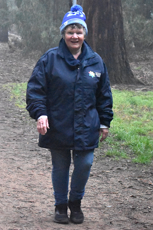 A woman wearing a blue coat, jeans, black boots, and a Big Freeze beanie walks in front of a foggy background.