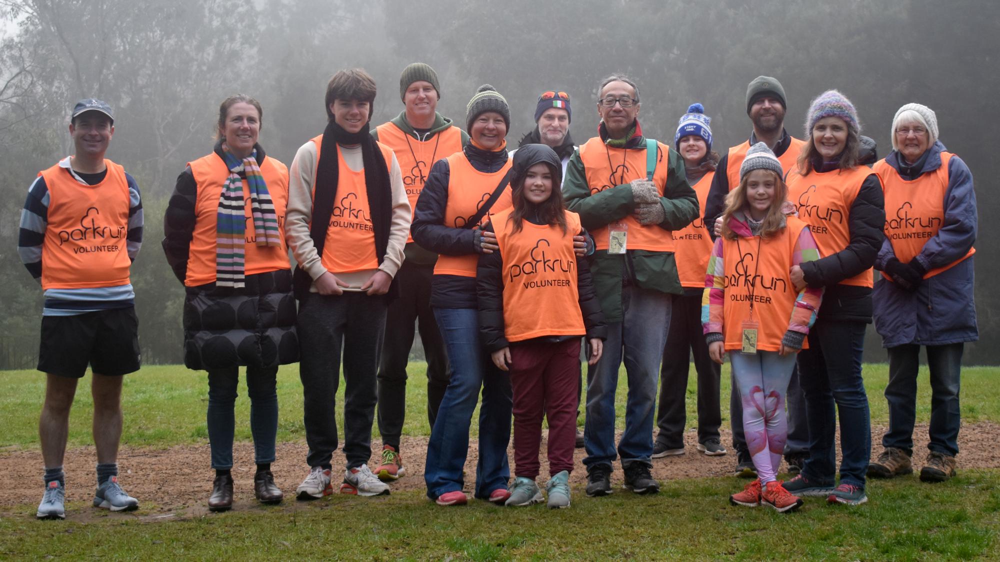 A group of thirteen volunteers wearing bright orange volunteer vests line up for a group photo.