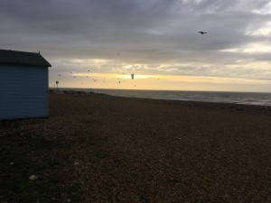 Pebbles, sea with many kitesurfers, one blue beach hut and cloudy sky with orange sunlight breaking through