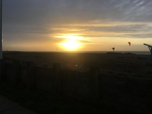 Sunrise over beach, with a kitesurfer in the distance and the wooden fencing at the front, pebbles in between