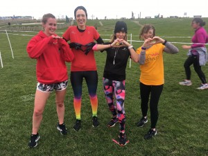 Carlyn and three friends post-run, all making heart shapes with their hands