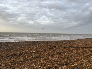 Beach with pebbles and rough grey sea, clouds above, a kitesurfer in the sea