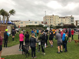 Lots of runners gathering by the fence on the green to hear the briefing