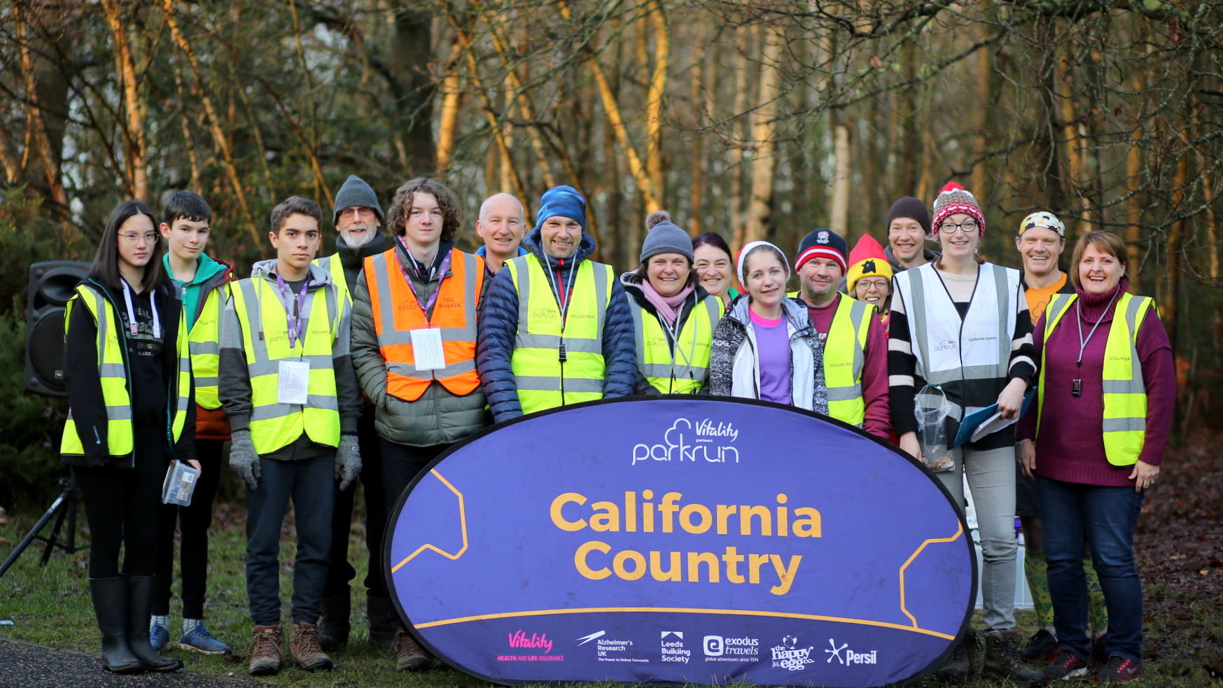 David and 15 other volunteers stand in a line behind the California Country parkrun sign all wearing high visibility  vests