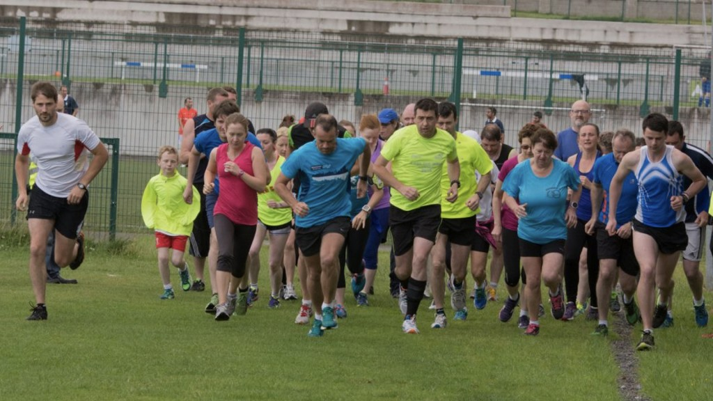 A mixture of runners start running towards the camera at the start of Athlone parkrun