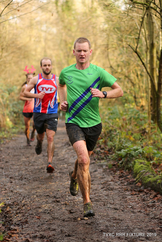 Fergal wearing his Reading Roadrunners kit runs  along a wooded path ahead of other runners.