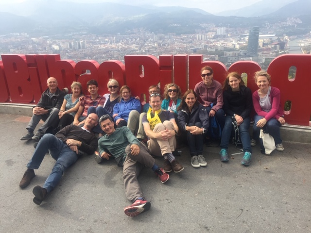 Fergal and thirteen friends sit on the ground in front of a red Bilbao sign high on a hill with he city in the background