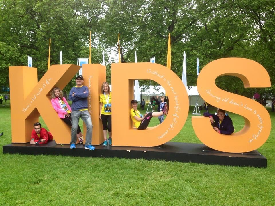 Sev and five friends sit in the letters of giant letters spelling our KIDS, at the Westminster Mile 2015