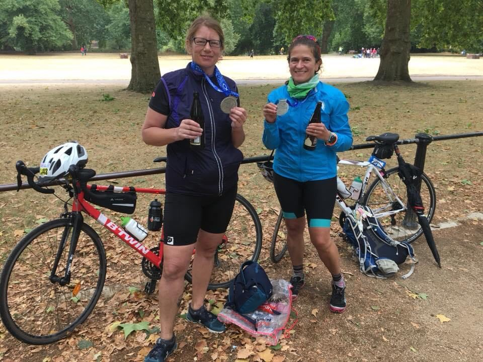 Sev and Teresa Caswell stand in front of their bikes in a park, and hold up their medals from Ride London 2018