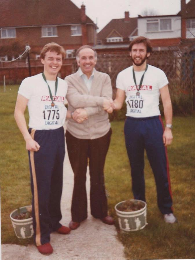 A young Ian and his brother stand in the running t-shirts and with their finishers medals, shaking hands with their father after the first Reading Half Marathon