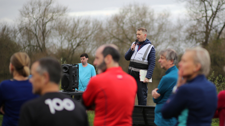 David stands on a bench with a microphone in his hand as he speaks to a crowd of runners in front on him