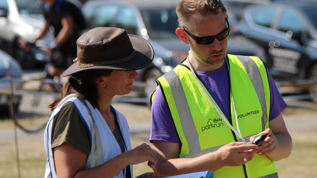 David looks and points at a stopwatch in his hand whilst Event Director Teresa Caswell looks on intently