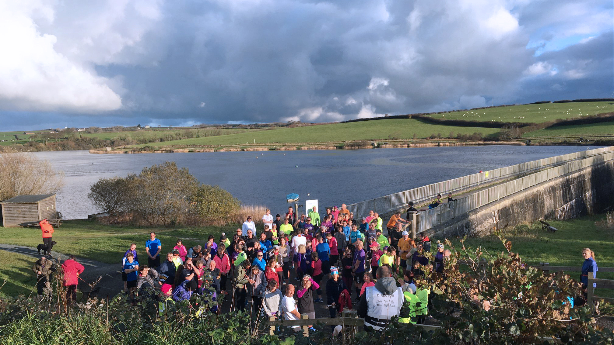 A Run Director in the foreground gives a briefinng to runners assembled in front of him in brightly coloured clothes with the expanse of Tamar Lake in the behind them all.